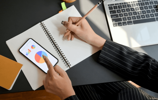 hands are shown using a pencil and paper while looking at a phone with a graph on it