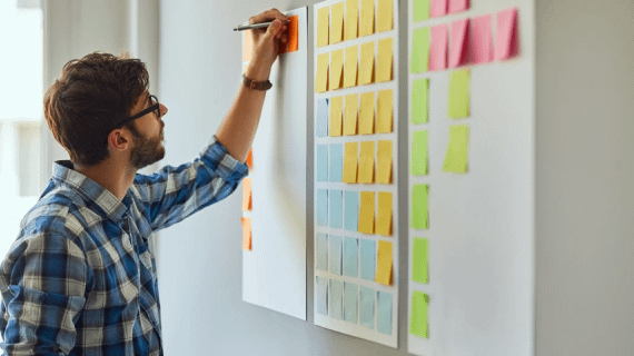 man stands near a large board full of sticky notes, writing on one